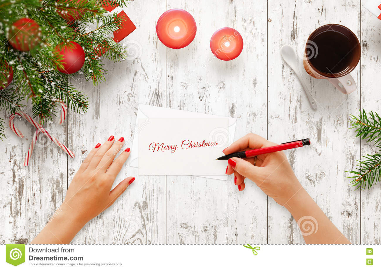 Woman write Christmas greeting message on paper