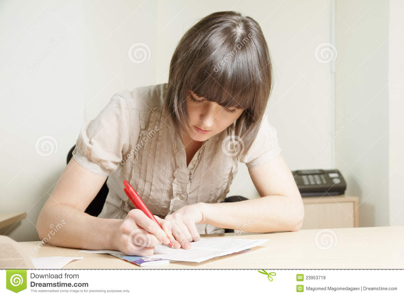 Young brunette woman writing on paper sheet at office desk.