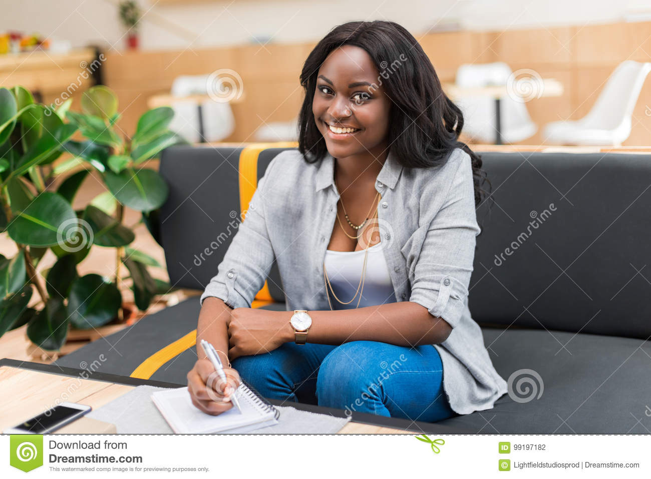 Woman writing something in notepad while sitting in cafe