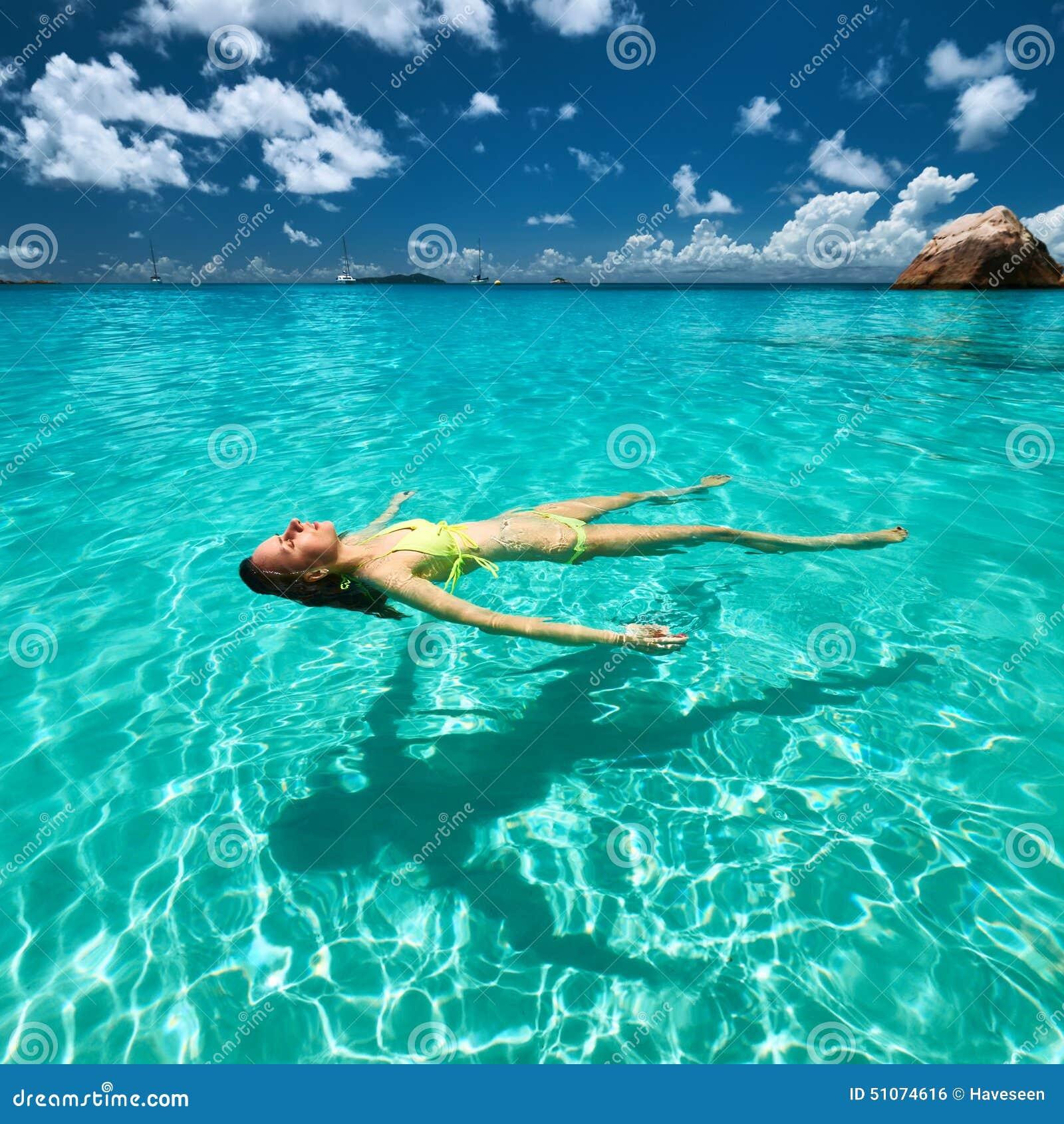 Woman In Yellow Bikini Lying On Water Stock Photo
