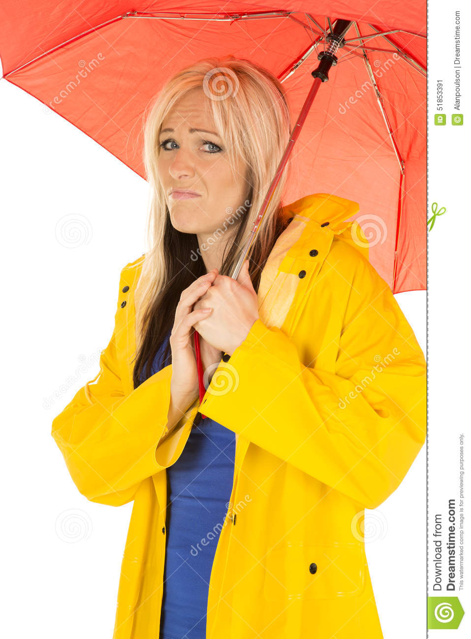Woman in yellow rain coat under red umbrella sad