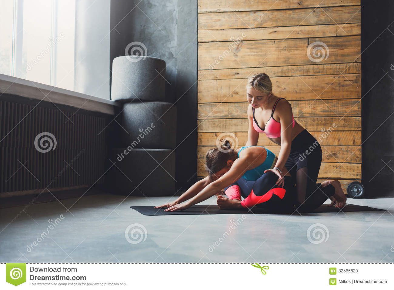 Woman with yoga instructor in class, asana cobbler pose