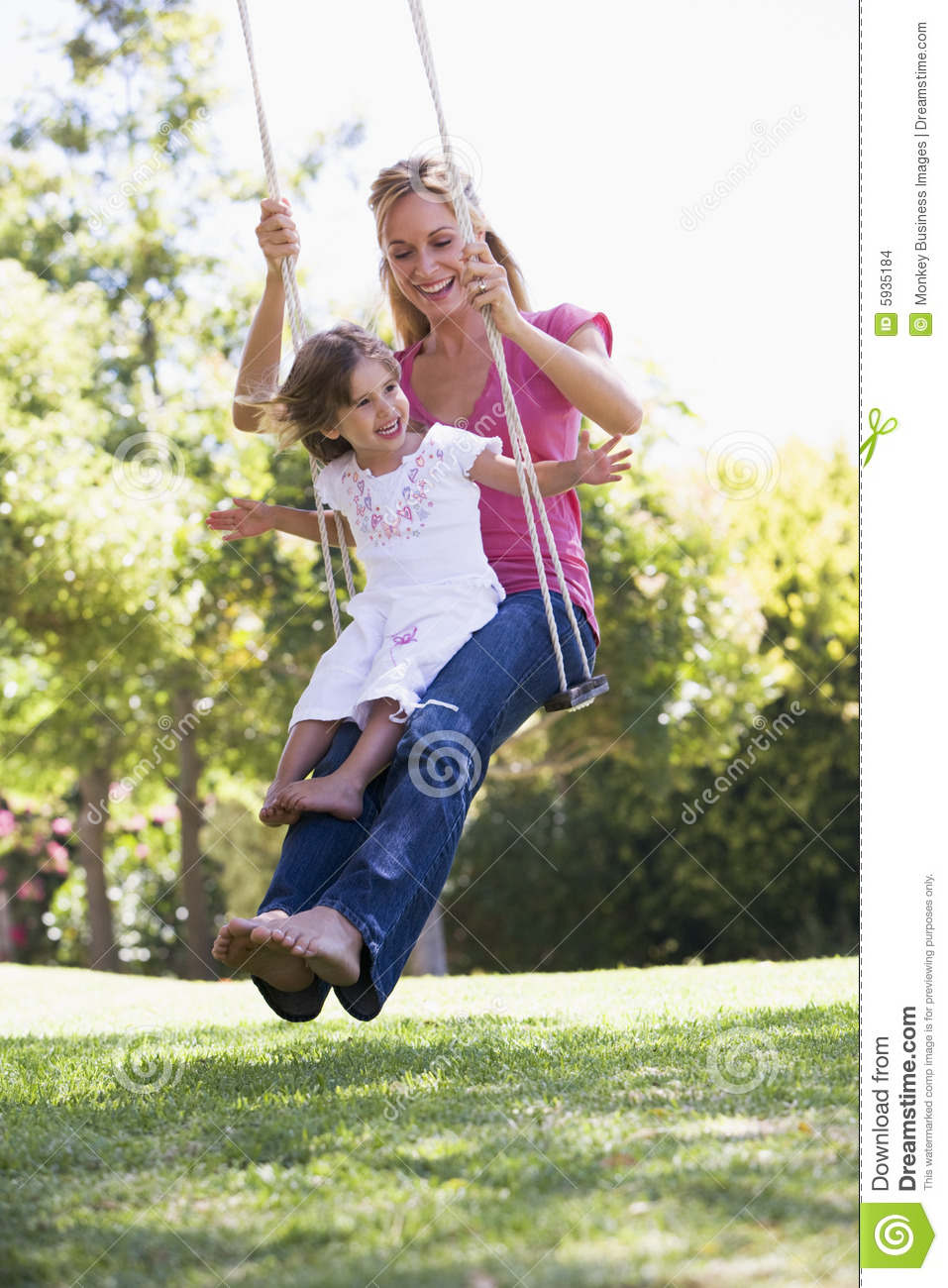 Woman and young girl outdoors on tree swing