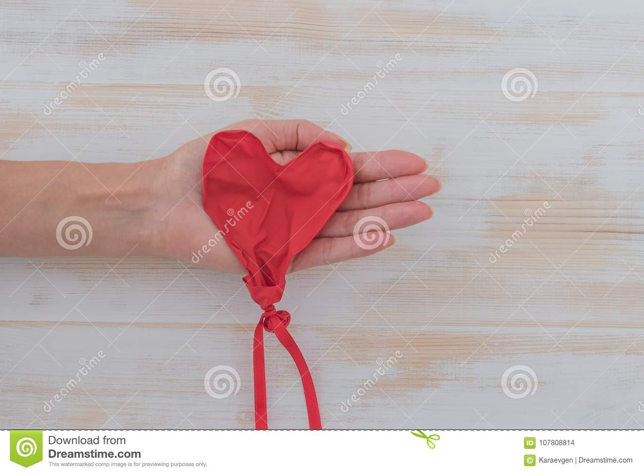 Womans hand with deflated heart shape balloon