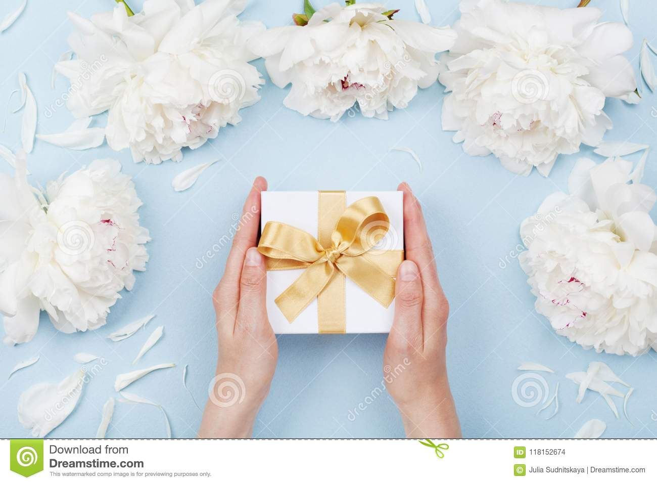 Womans hands giving gift or present box decorated white peony flowers on pastel table top view. Flat lay composition for birthday