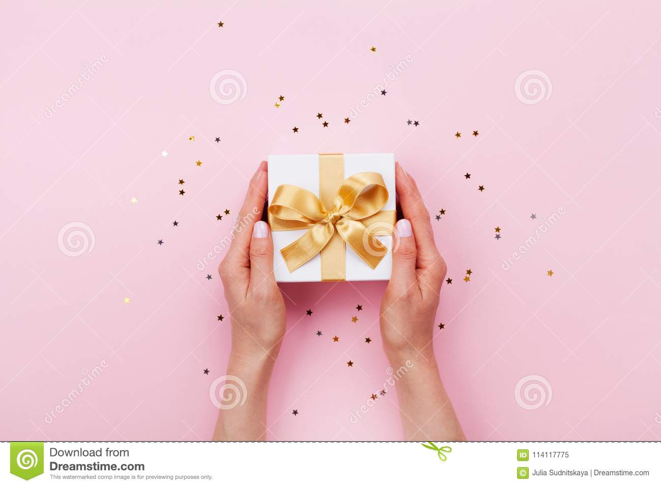 Womans hands holding gift or present box decorated confetti on pink pastel table top view. Flat lay composition for birthday.