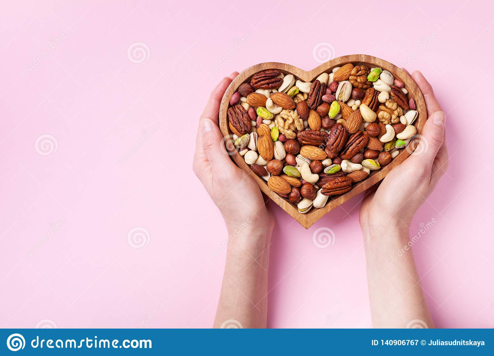 Womans hands holding heart shaped bowl with mixed nuts on pink table top view. Healthy food and snack. Flat lay