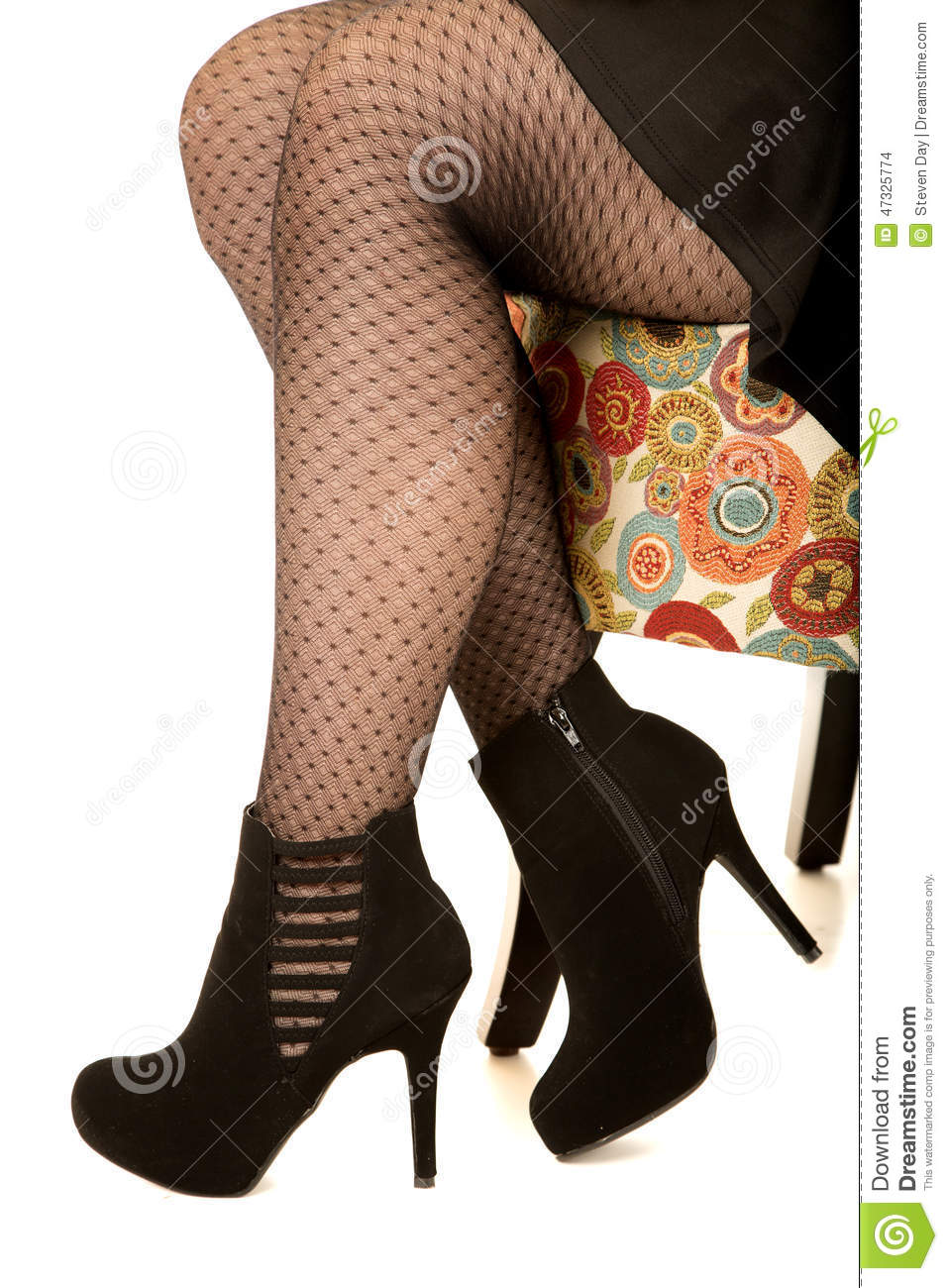 514e193460b4 Womans legs in fishnet style stockings sitting on floral pattern chair wearing  black heels