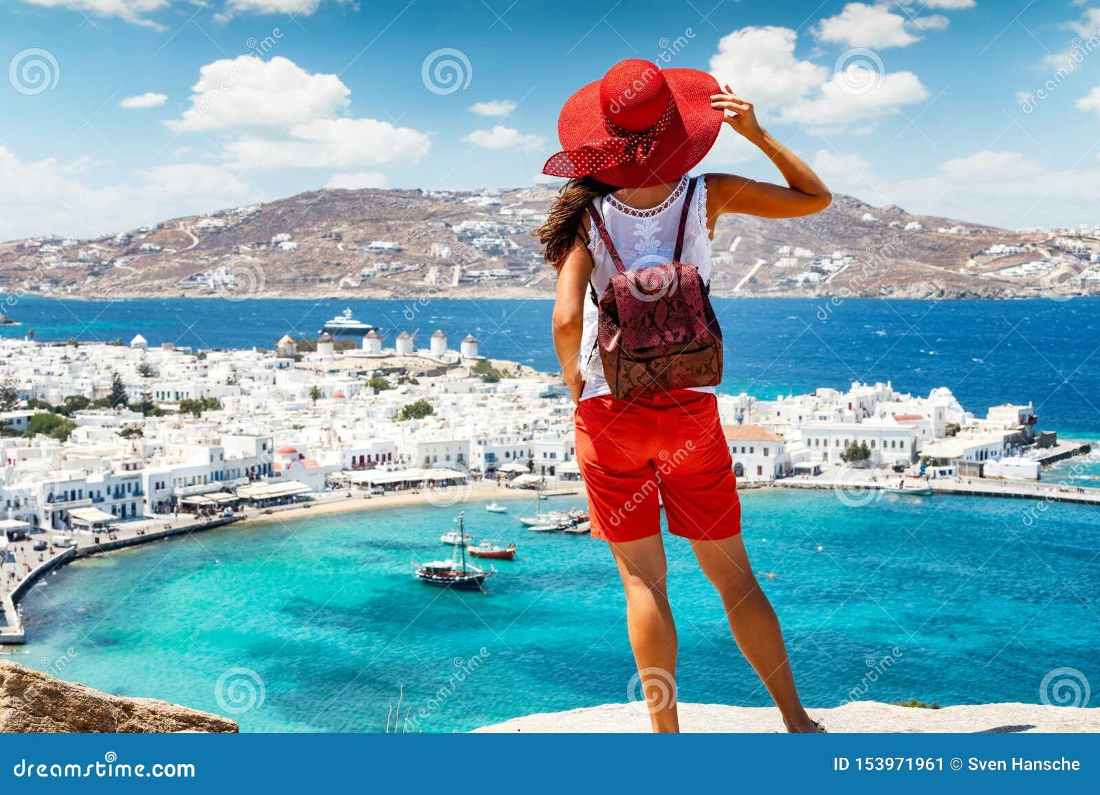 Womanstands op een heuvel over de mooie stad van Mykonos-eiland