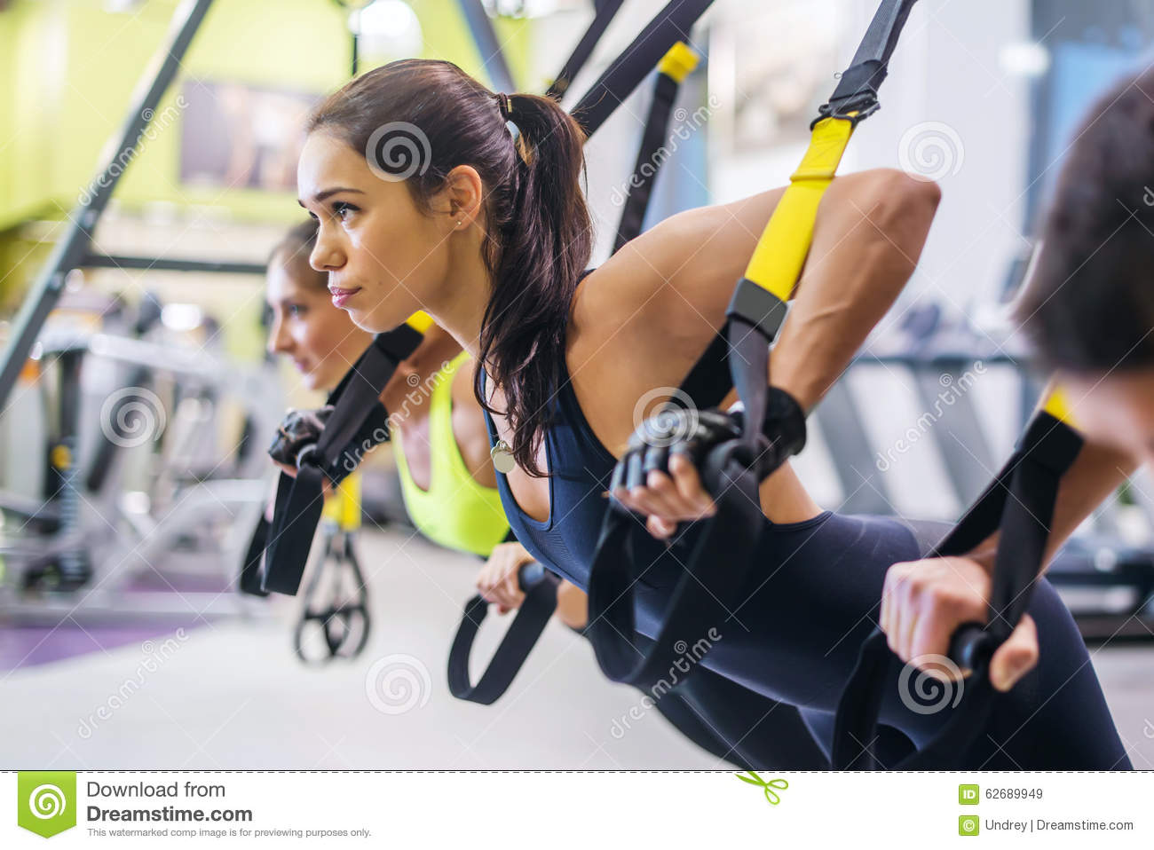 Women doing push ups training arms with trx