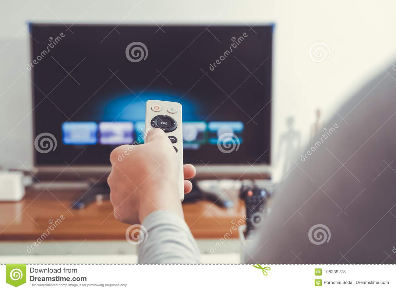 A women hand hold the remote control of the TV box in the living room 658204d2dd