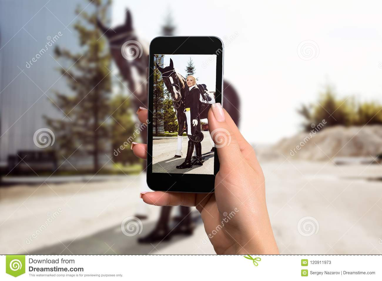 Women hand holding mobile smartphone taking picture of woman rider with a horse.