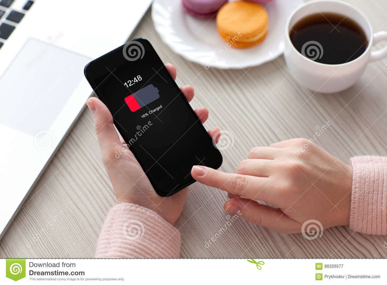Women hands holding phone with low charged battery screen