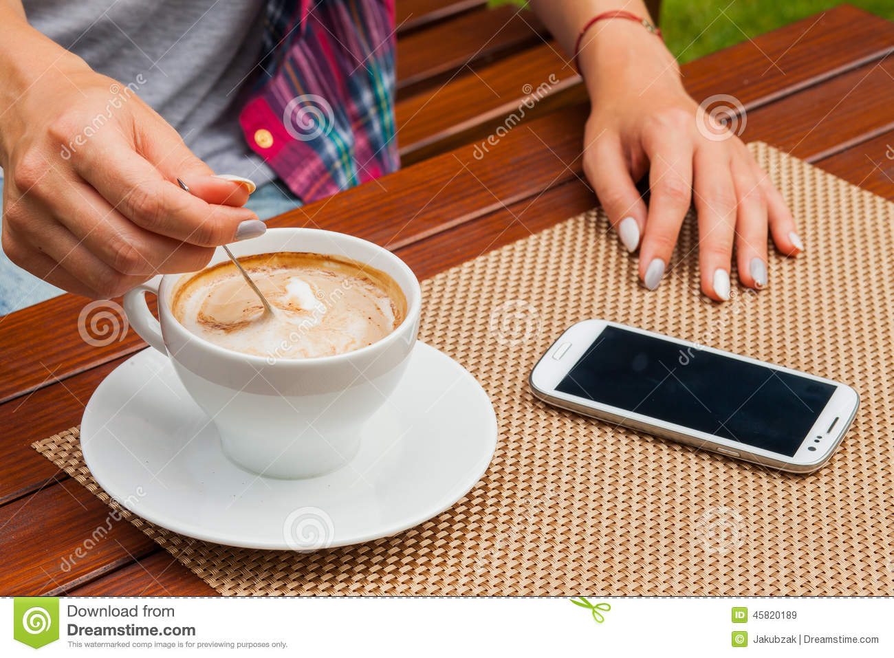 Coffee and mobile phone on table stock photo image 45820430 women hands with mobile phone coffee on the table outdoor photo royalty free stock images geotapseo Gallery