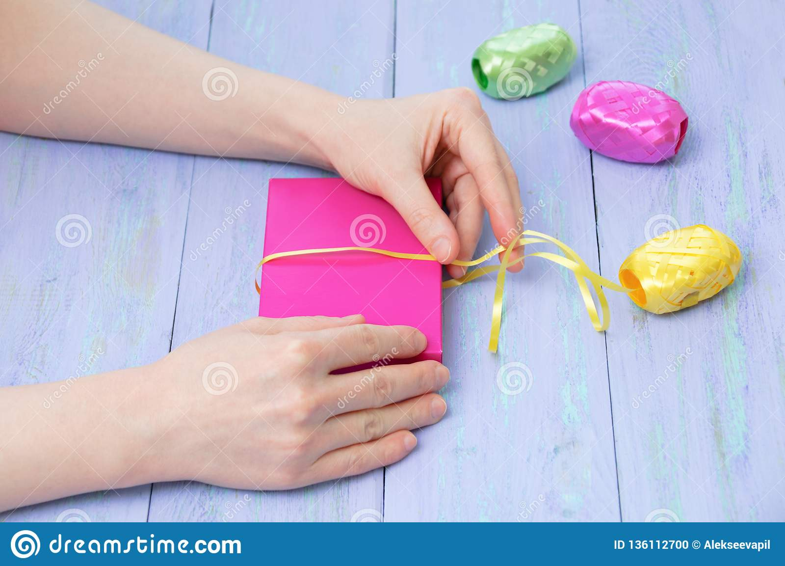 Women hands wrapped in a pink gift box with a yellow ribbon violet wooden background. Cose-up