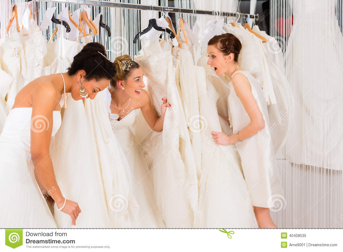 Women having fun during bridal dress fitting in shop stock for What to wear wedding dress shopping