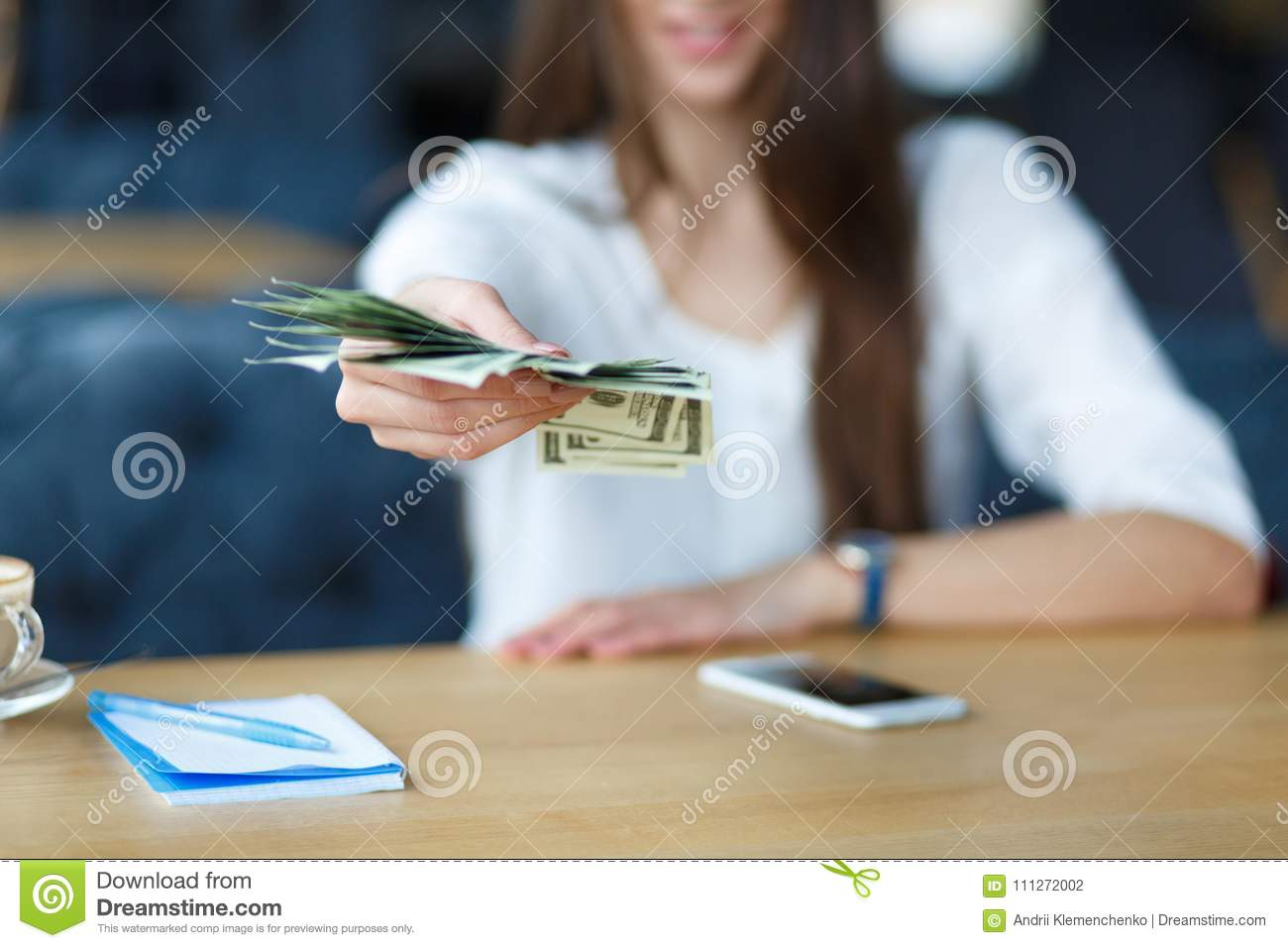 Women holding dollar on hand and seating against. Business concept
