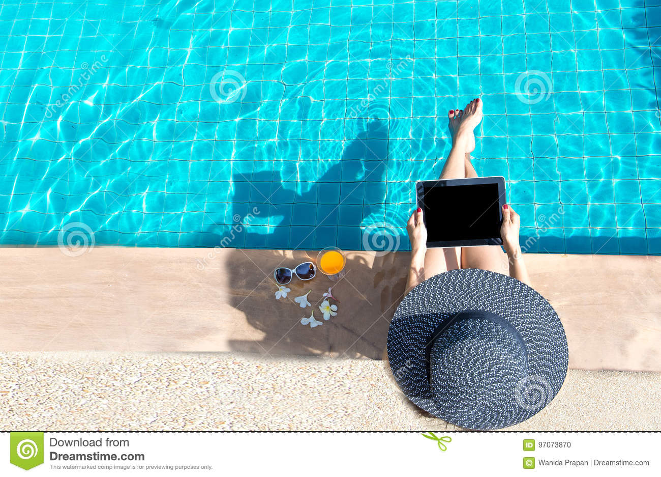 Women lifestyle play laptop relaxing near luxury swimming pool sunbath, summer day at the beach resort in the hotel.