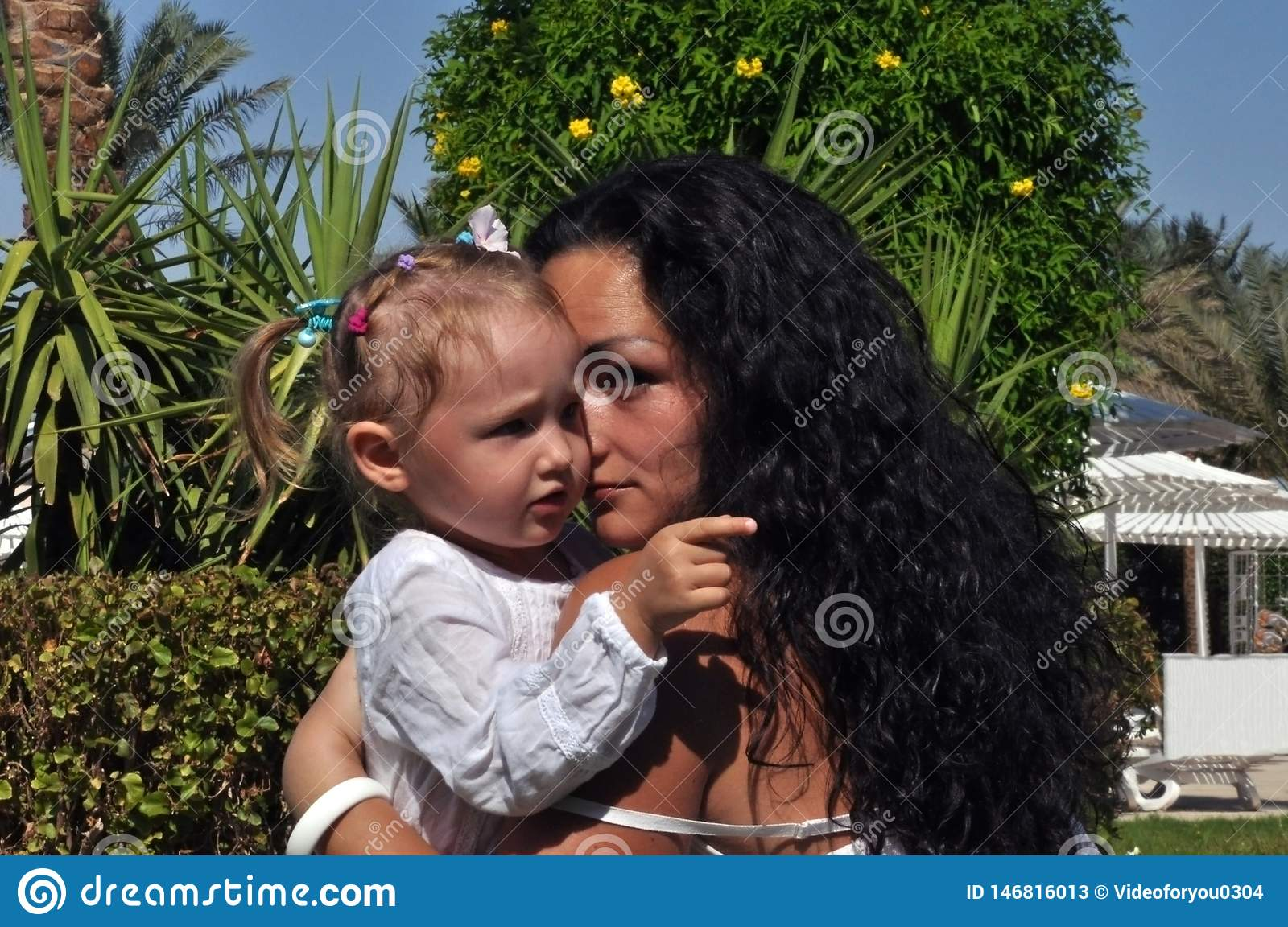 A woman with long, black curly hair embraces her daughter on a sunny day.