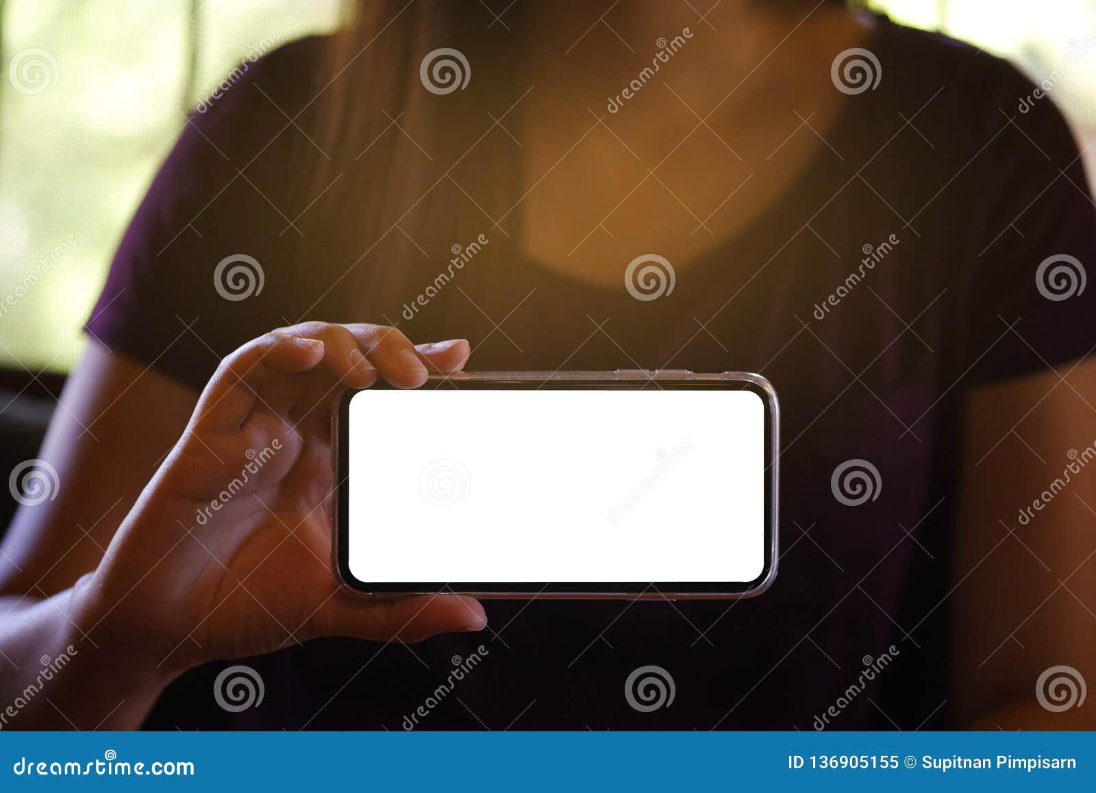 Women& x27 ; mains de s tenant l écran vide de téléphone portable en avant pour l écran de l espace de copie téléphone intelligen