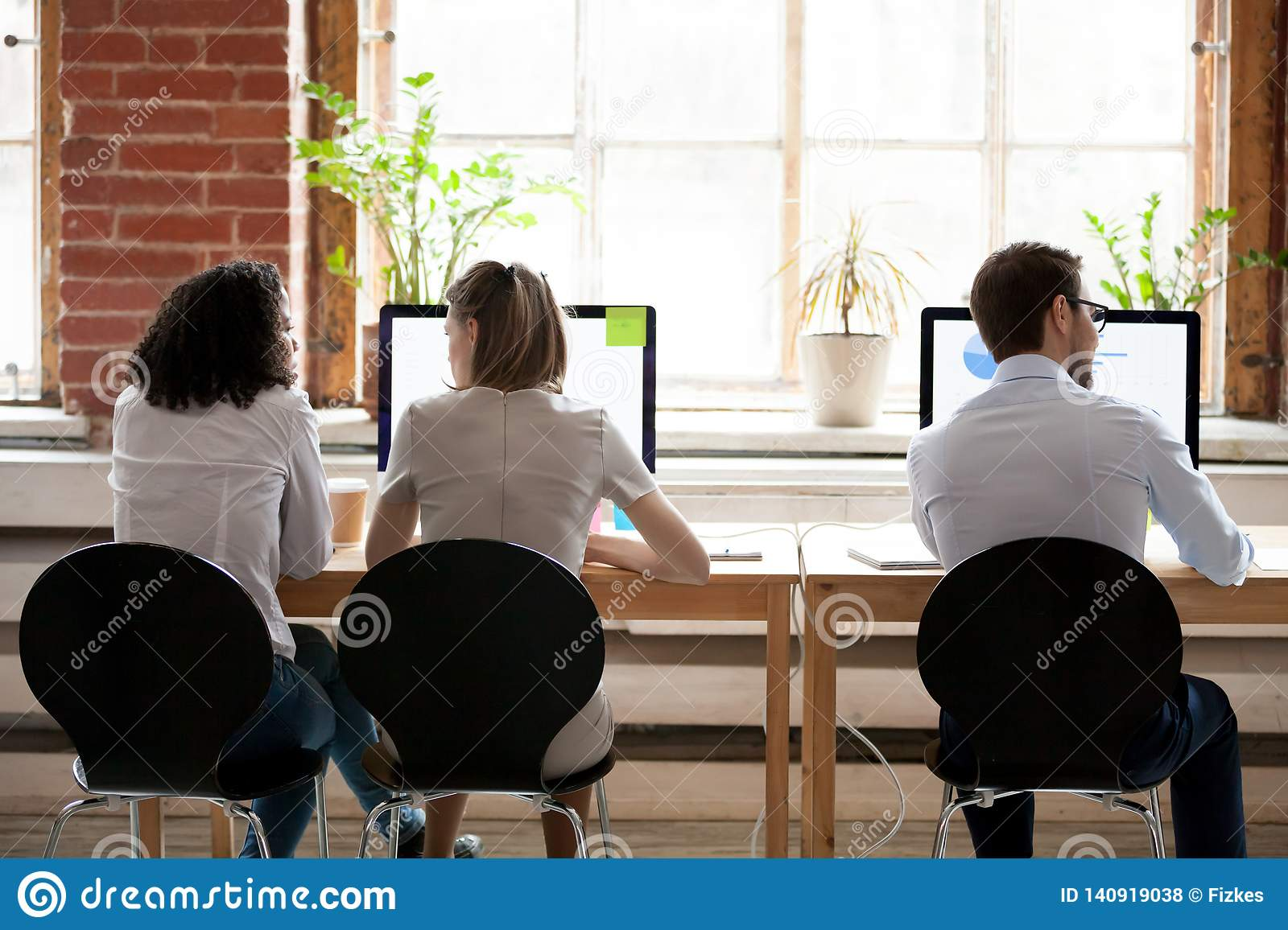 Women and man sitting in shared office rear back view
