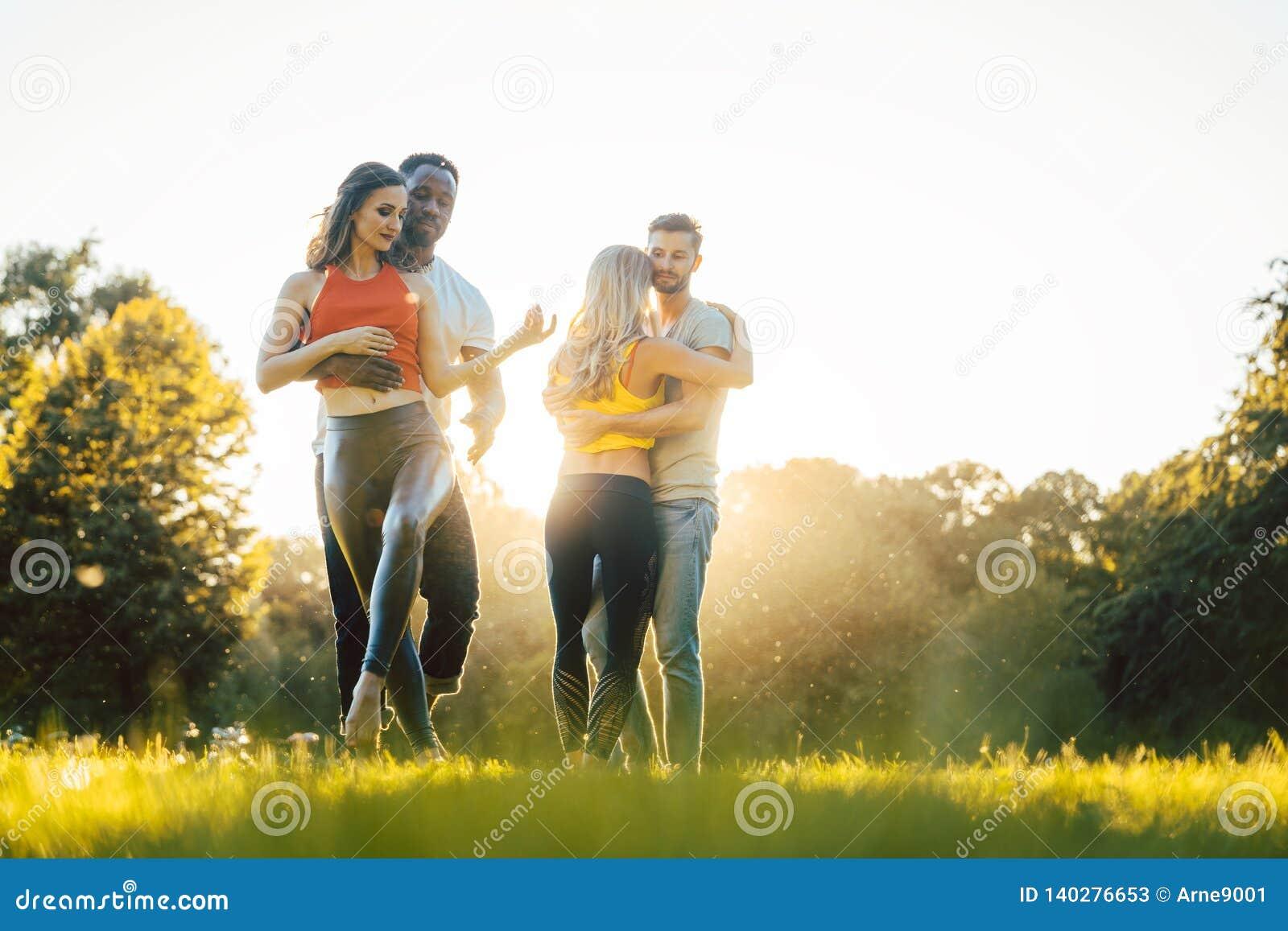 Women and men having fun dancing in the park