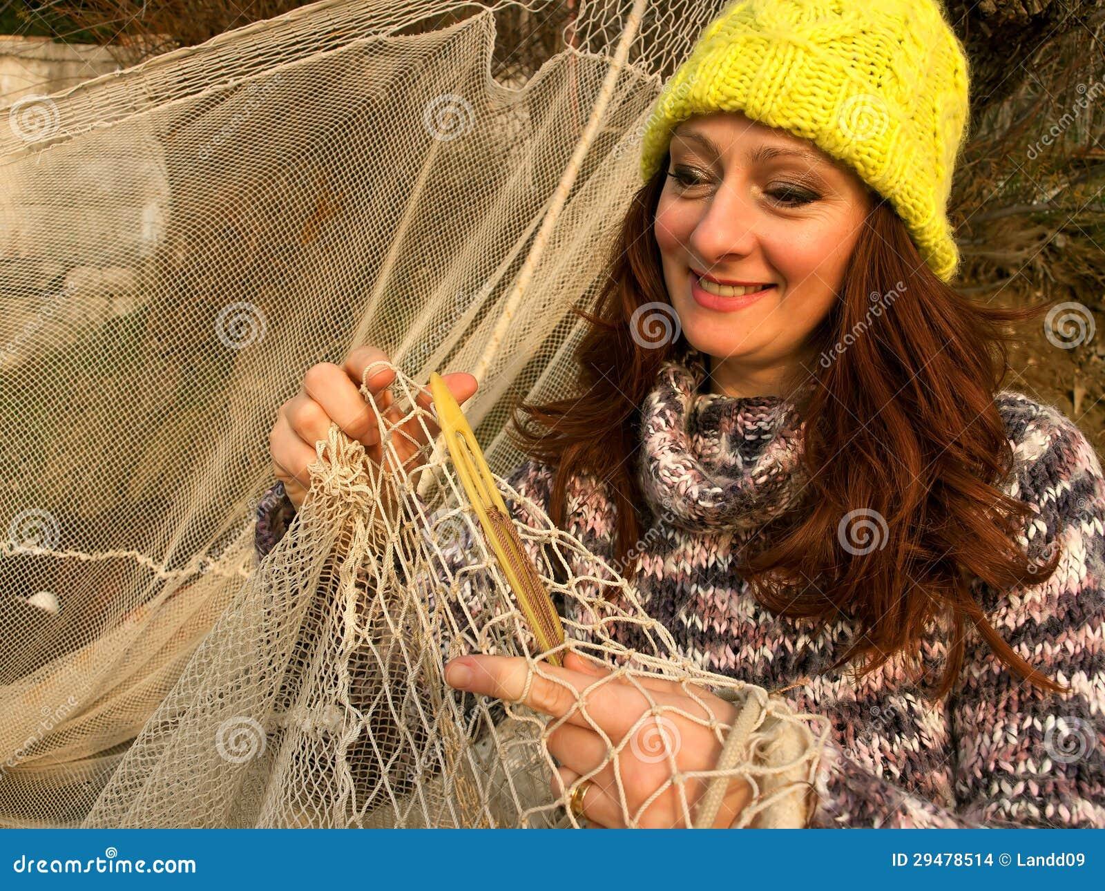Women mend a fishing net