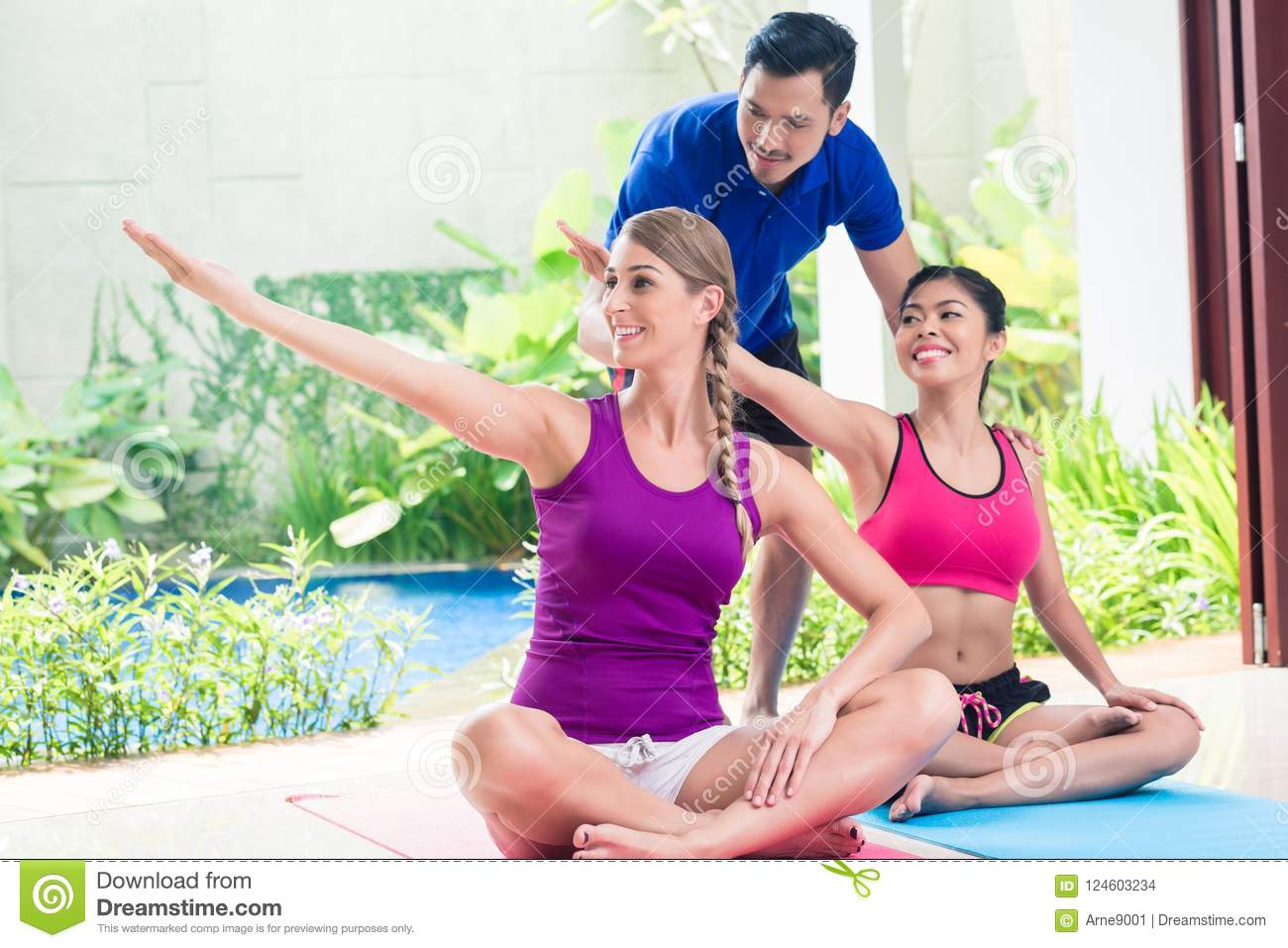 Women and personal trainer at fitness exercise