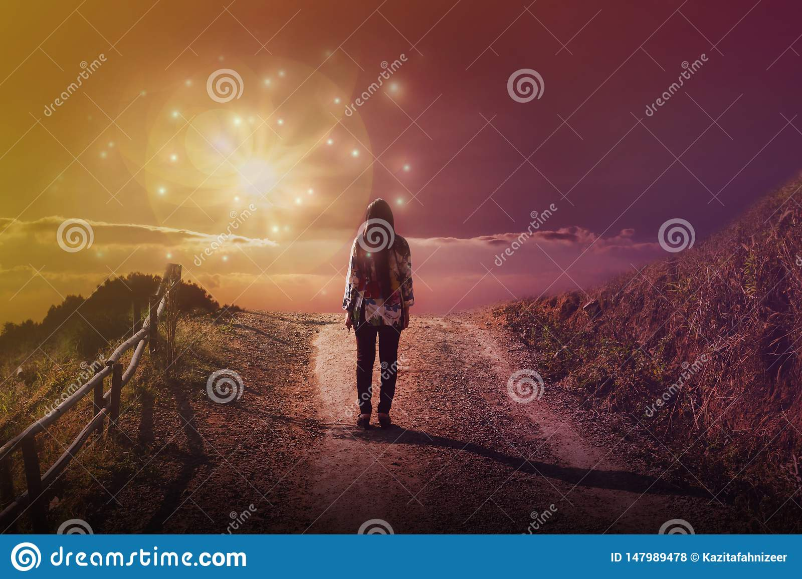 Women rare view standing in front of God sun light flare with dreamy fantasy sky and cloud, women at end of street or way