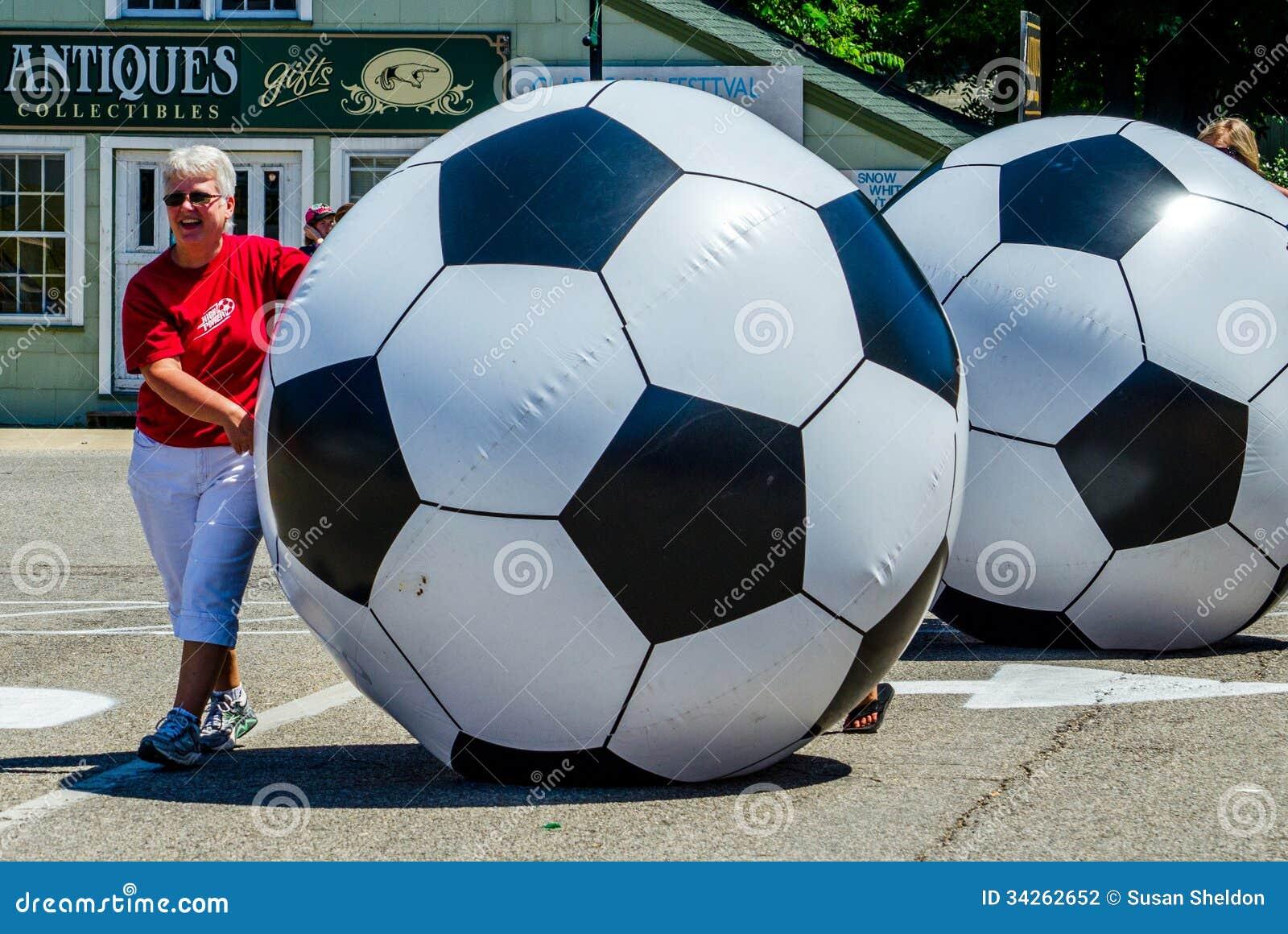 Women rolling giant soccer balls moms roll down street peach festival