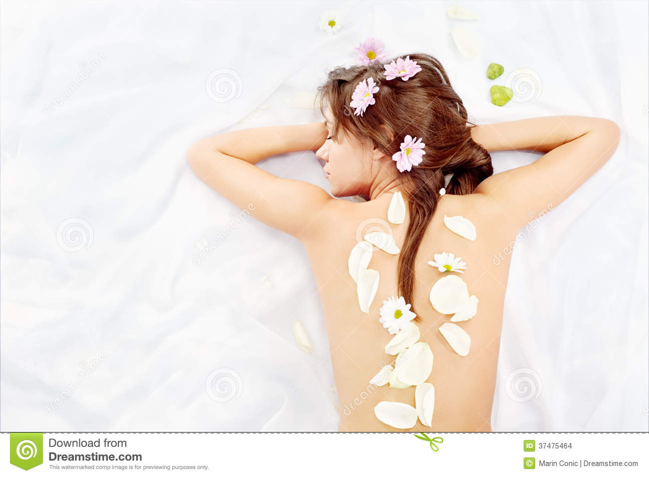 Women s back covered with petals and flowers