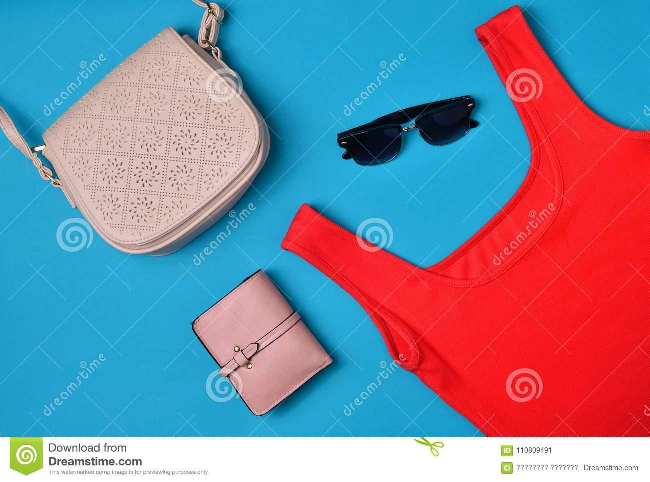 Women& x27;s clothing and accessories laid out on a blue background. Red T-shirt, purse, bag, sunglasses Top View. Flat lay
