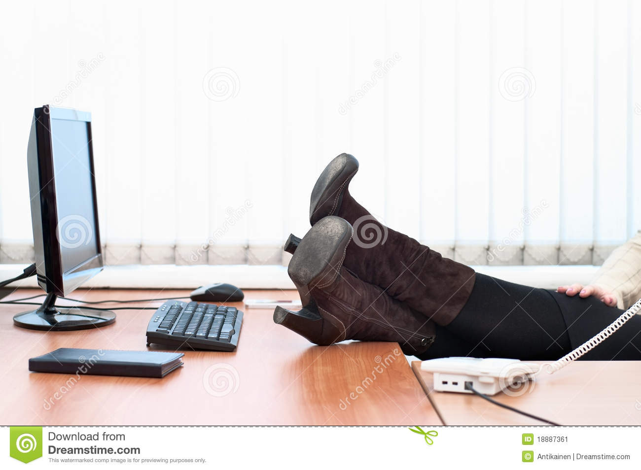 Women S Feet In Boots Lies On The Desktop Stock Image