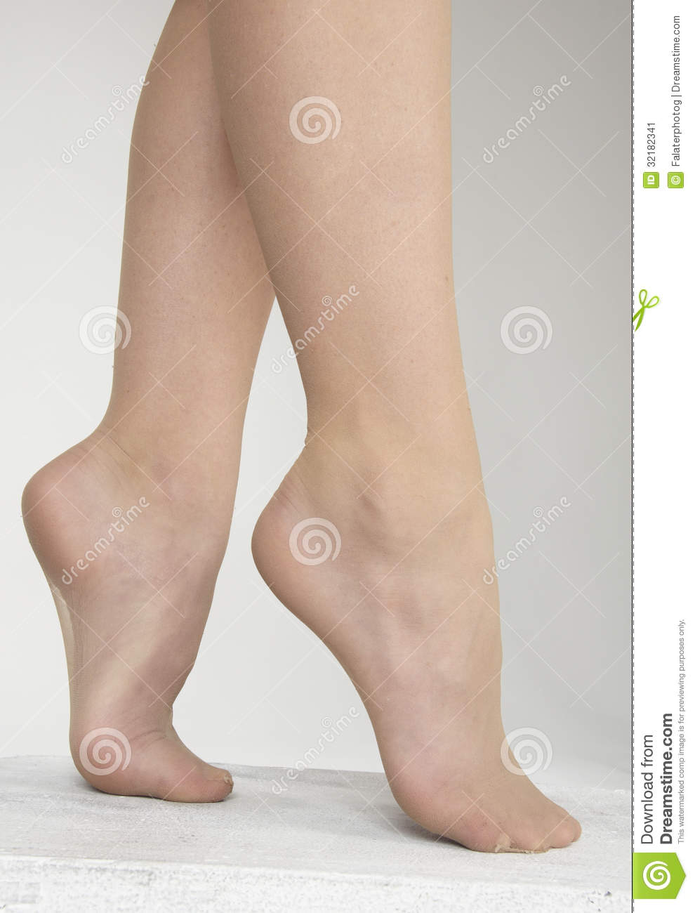 Close Up of woman's feet wearing sheer pantyhose against a white ...