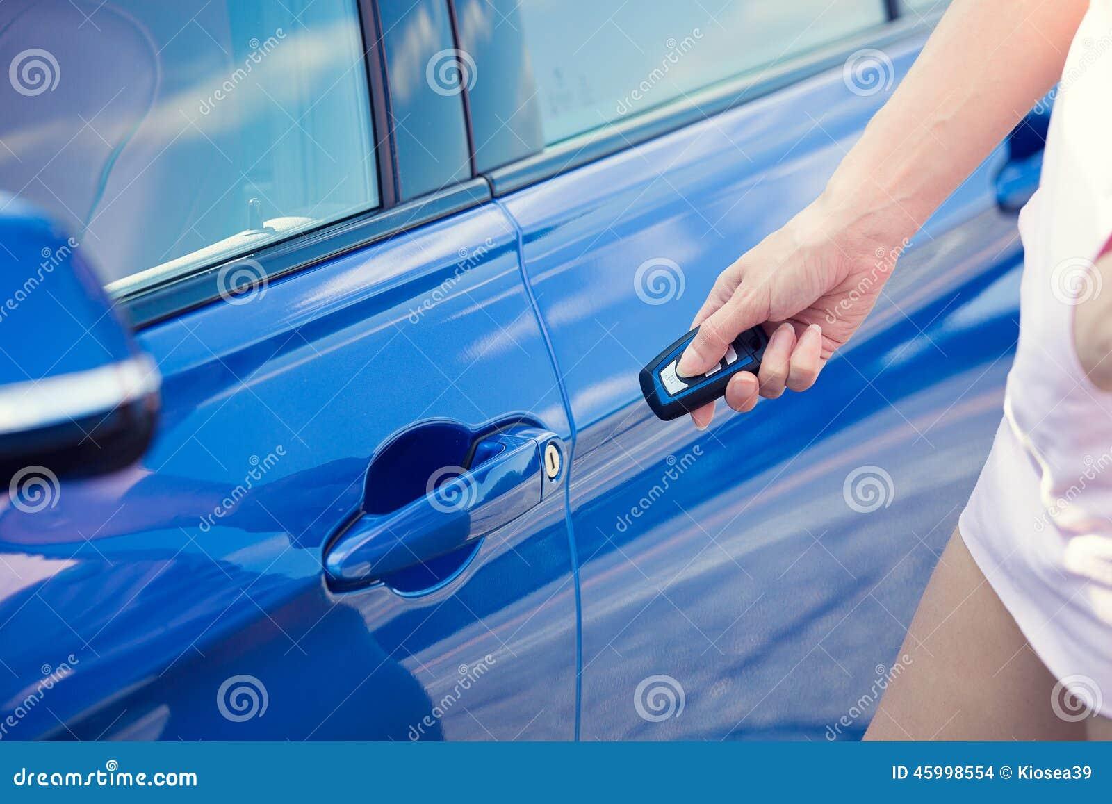 Women s hand presses on remote control unlocks car door