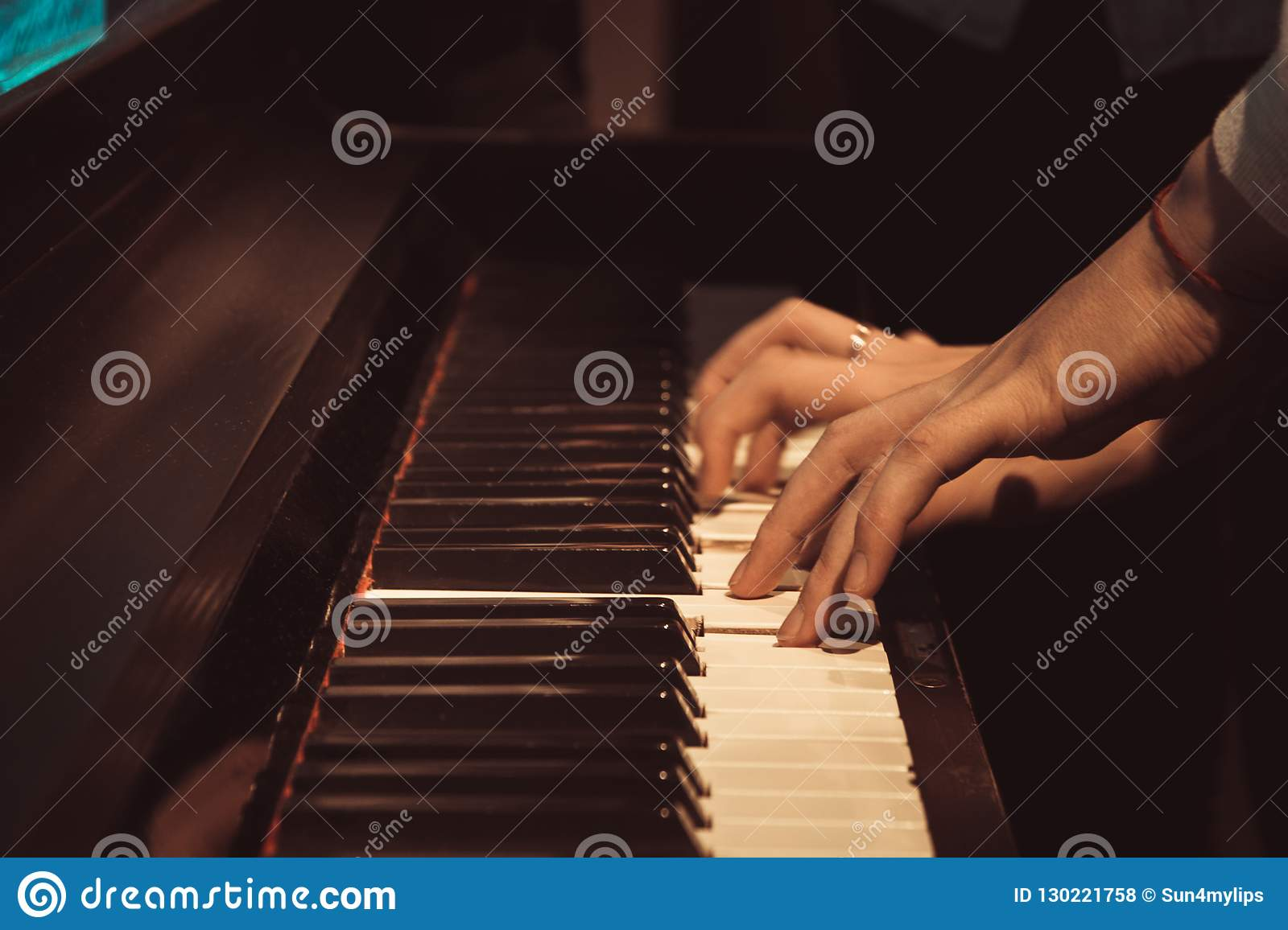 Women`s hands on the piano keys, playing a melody