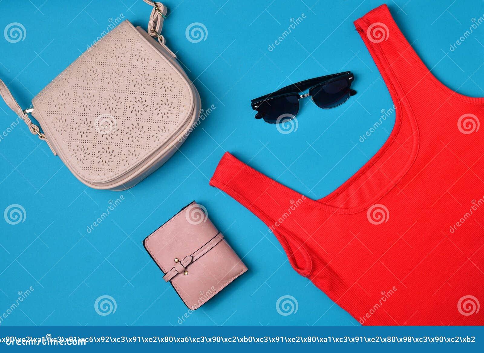 """Women& x27; s kleding en toebehoren die op een blauwe achtergrond wordt opgemaakt Rode T-shirt, beurs, zak, sunglassesï"""" Hoogste"""