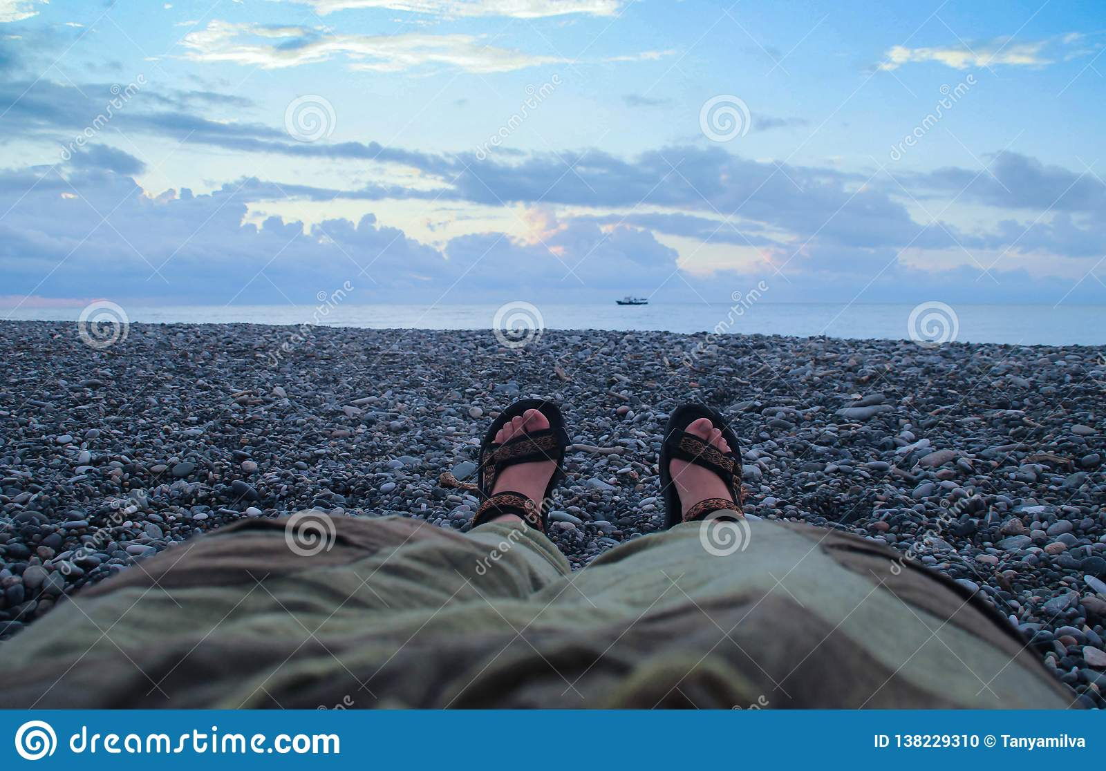 Women`s legs in pants and sandals on bare feet on the sunset zone above the sea lie on the beach