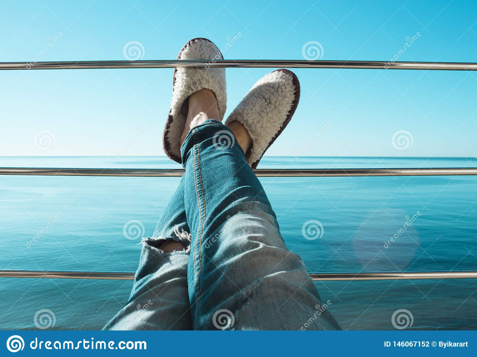 Women`s legs in torn jeans and white sheep fur slippers lying on the crossbar of the balcony