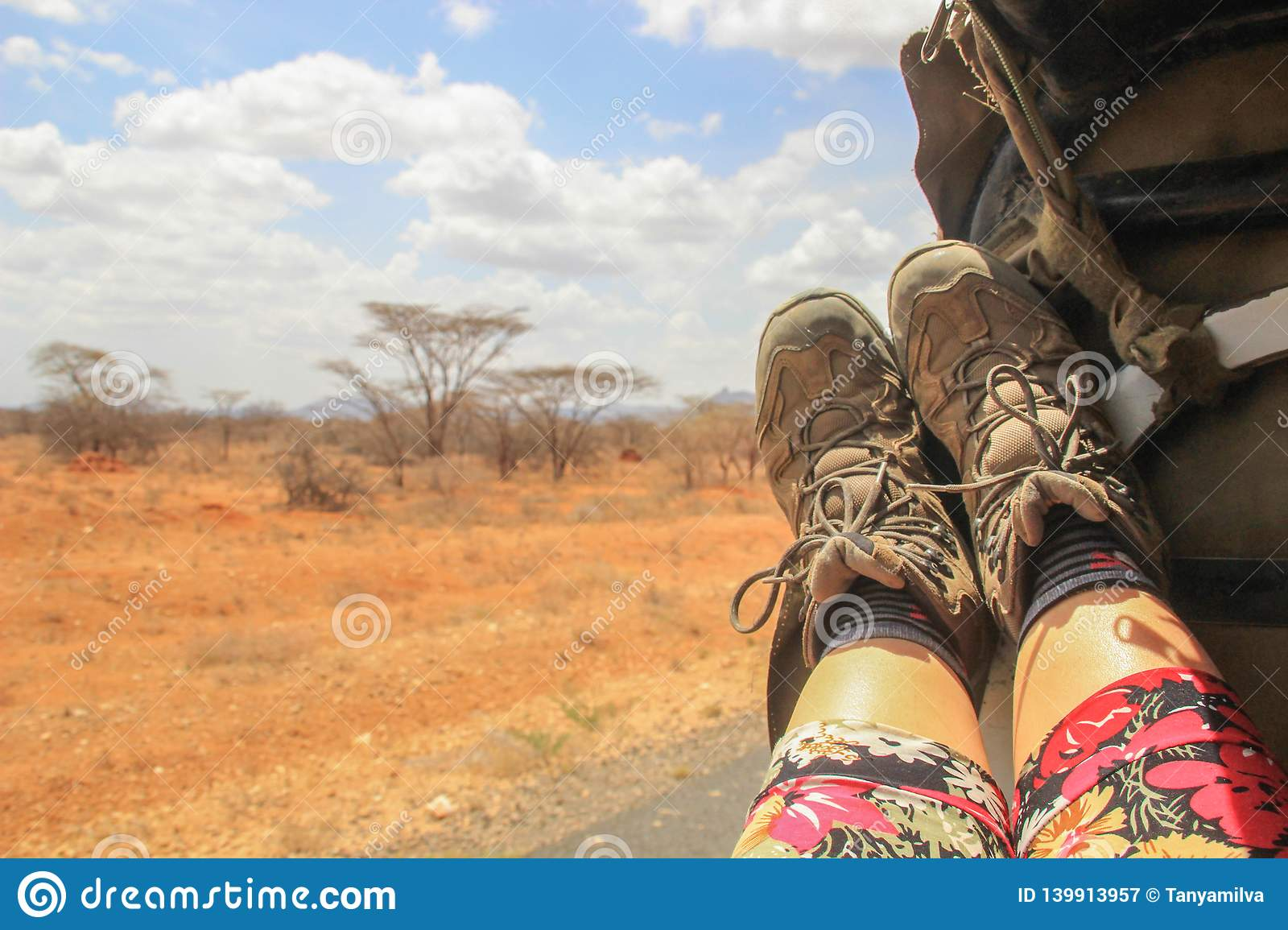 Women`s legs and tourist boots on the background of the African