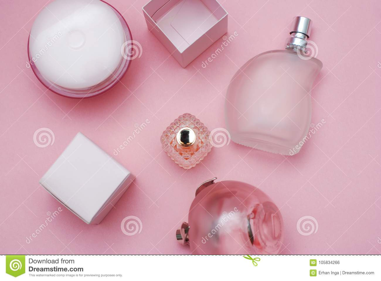 Women`s Perfumes Botles and Cosmetics in Beautiful Glass Bottle and on pink background. Fashion and Beauty Concept.