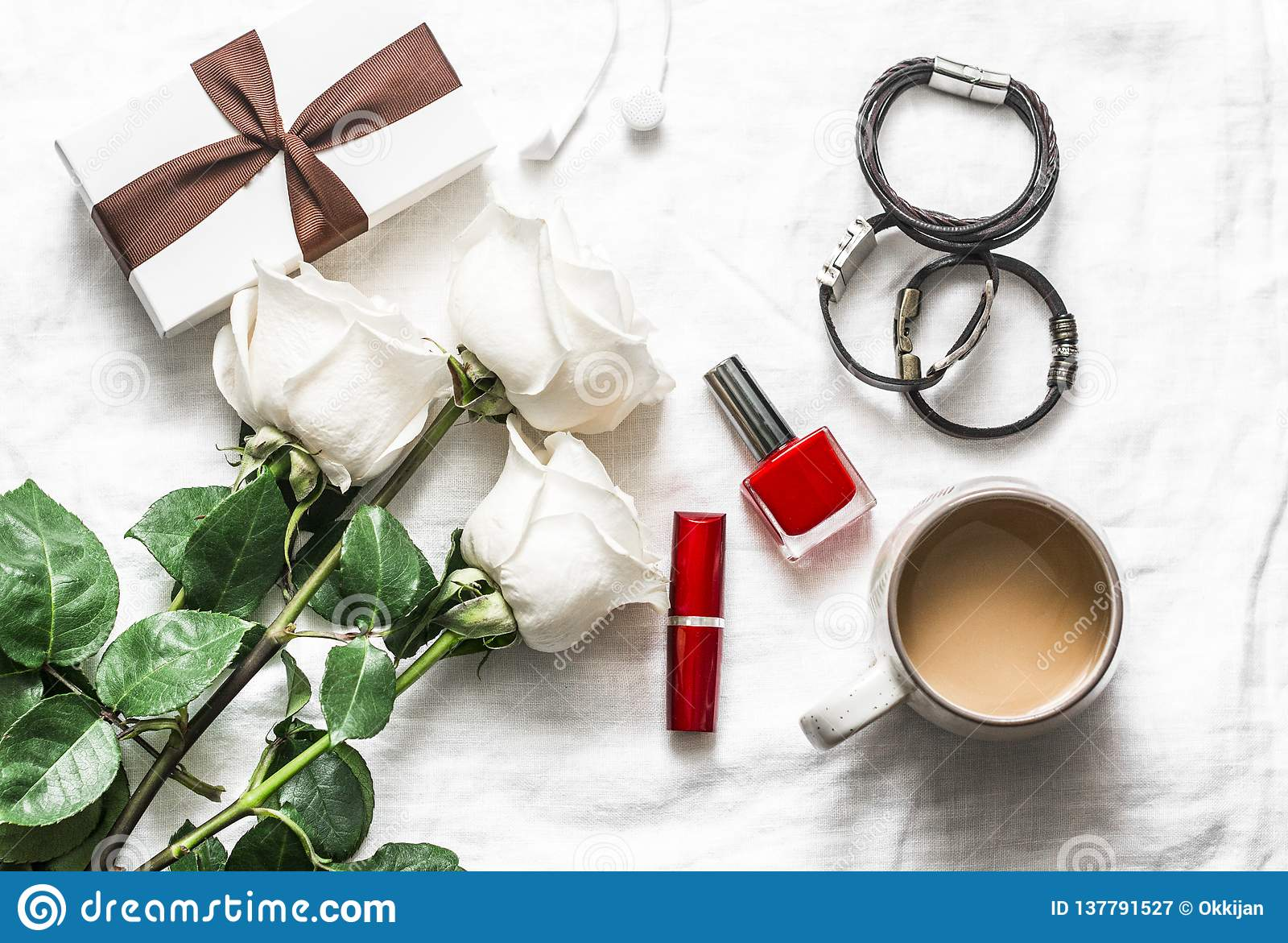 Women`s table beautiful background. Bouquet of roses, gift box, leather bracelets, lipstick, headphones, coffee on a light backgro