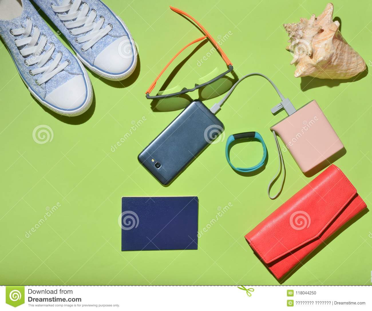 Women s trendy travel accessories and technology gadgets on the green  surface. Sneakers d8141fe1b2