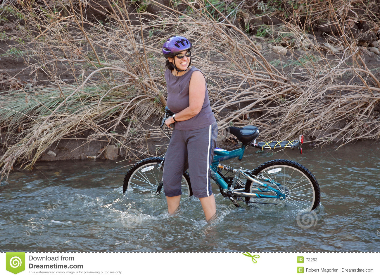Women in stream with bike