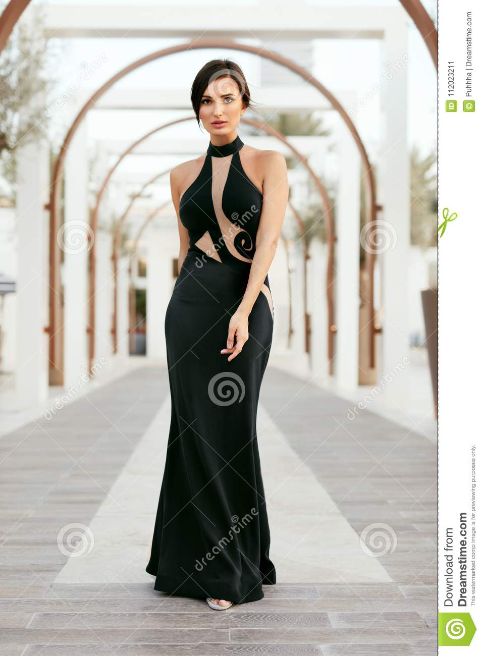 4cabbbd46768 Fashion Girl In Long Black Dress Posing Outdoors. Portrait Of Beautiful  Fashionable Female Model In Glamourous Evening Dress With Elegant Hairstyle  Posing ...