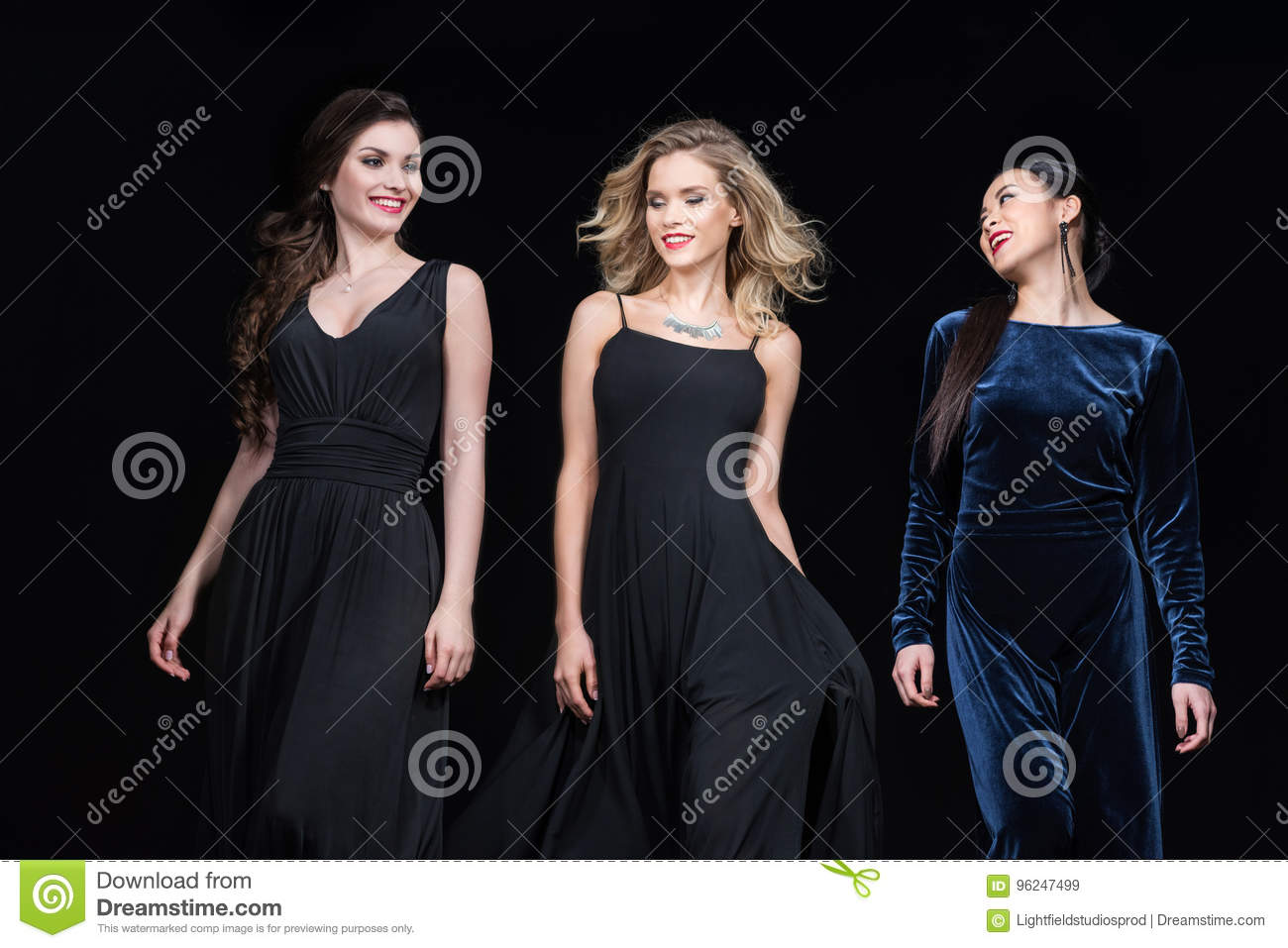 1f5cf37247e Cheerful women in stylish maxi dresses walking together isolated on black