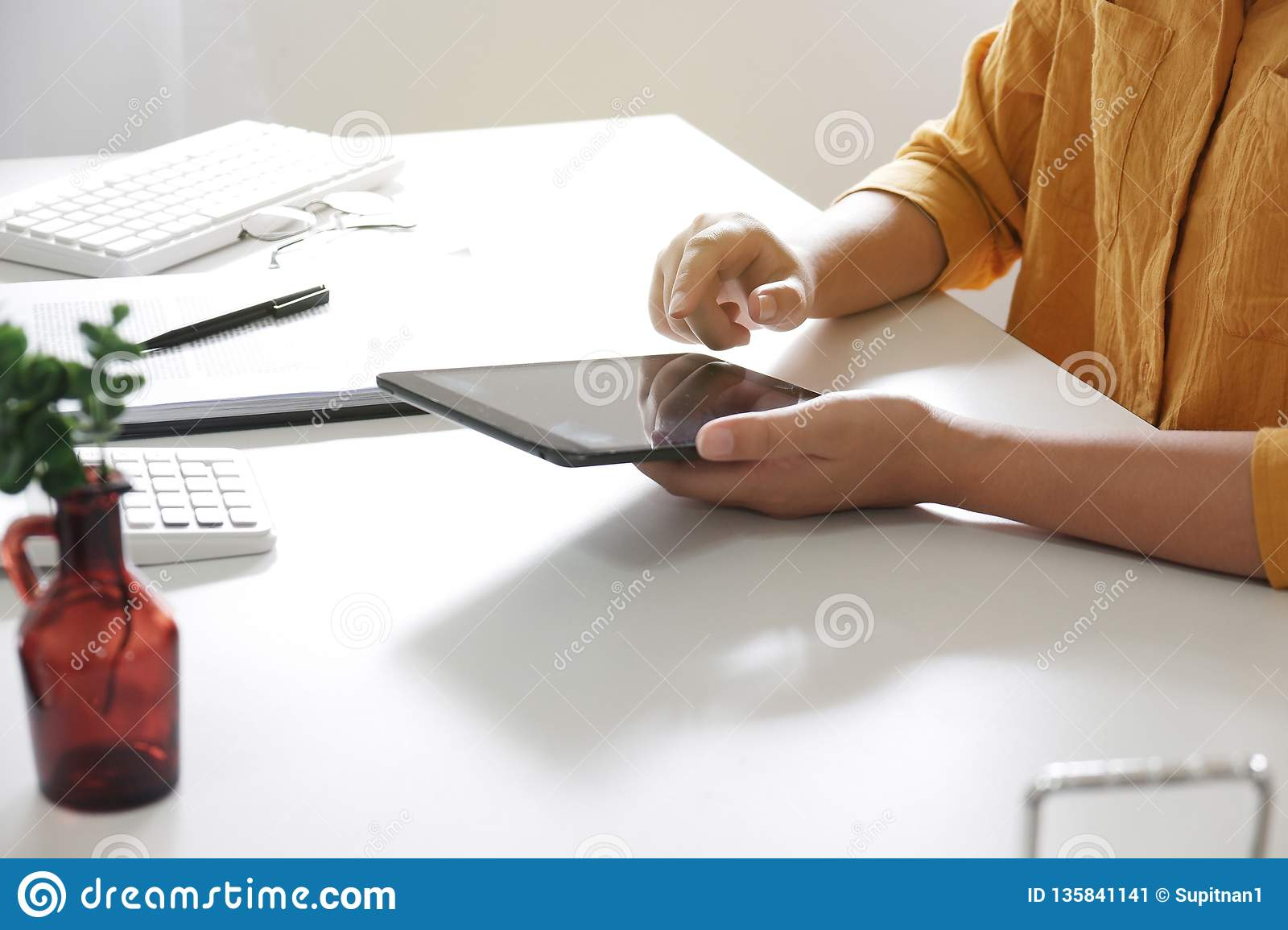 women using tablet while working in her office.