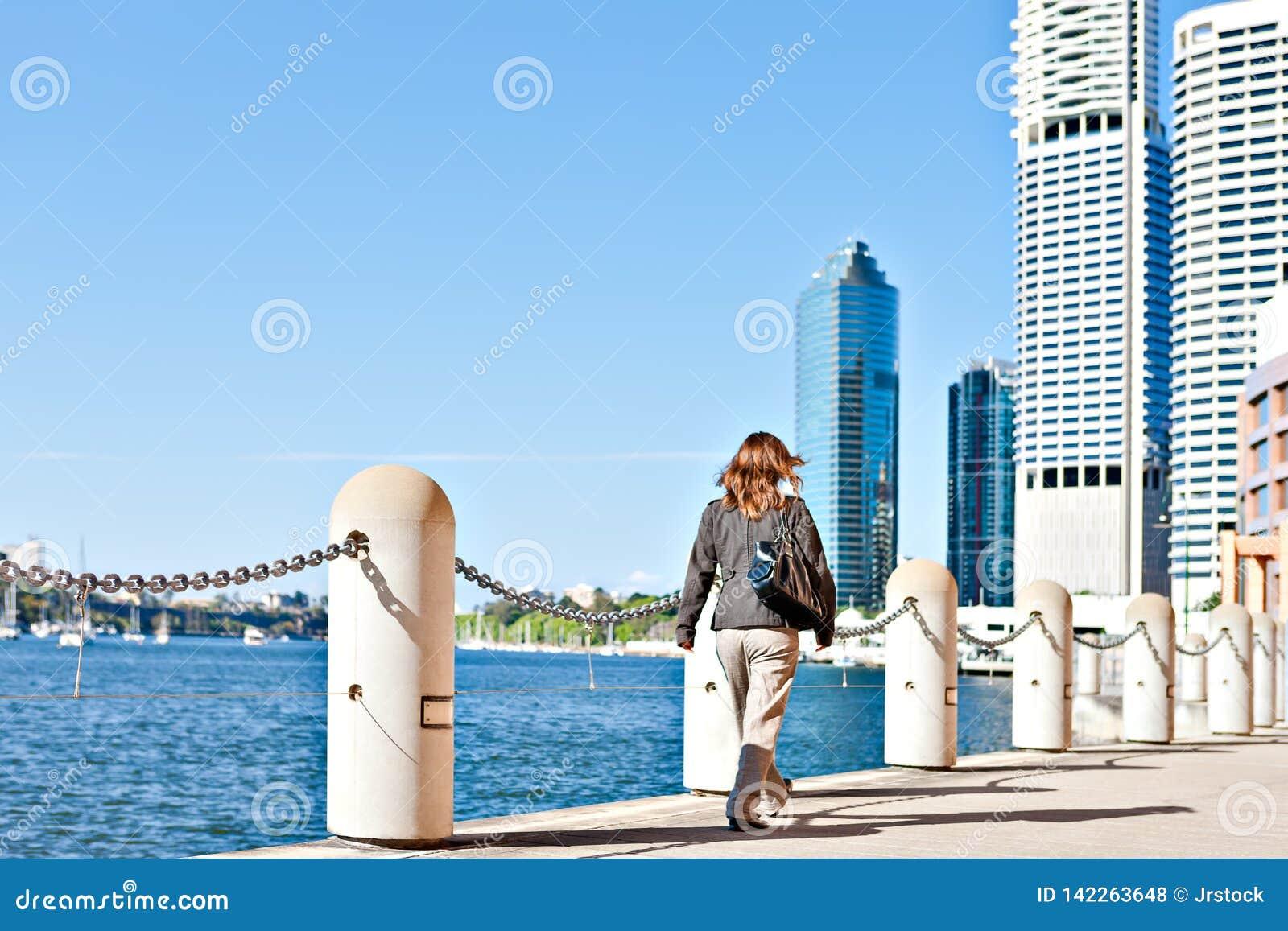 Women walk on the street near to a fence