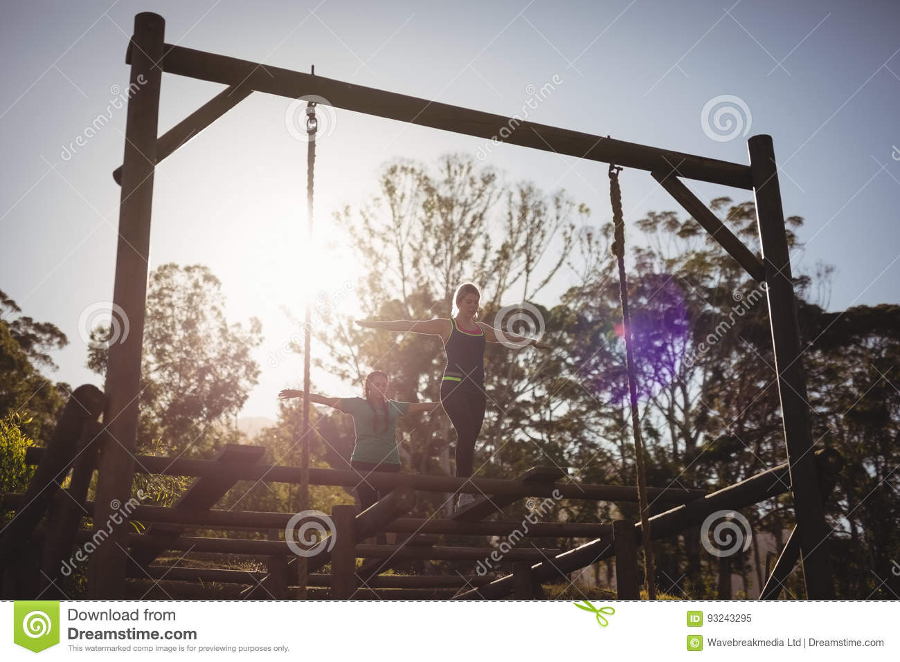 Women walking on outdoor equipment during obstacle course