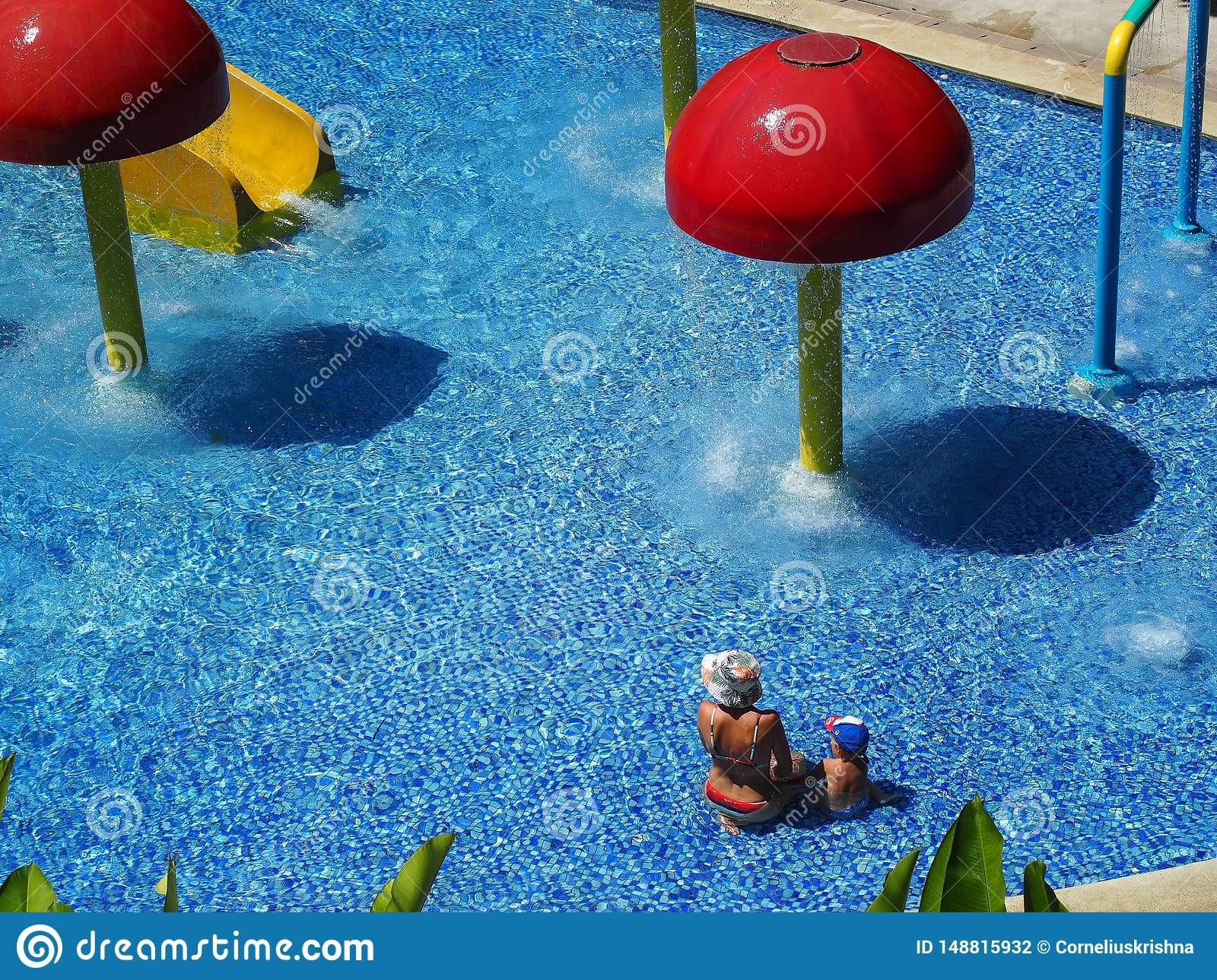 A women wearing bikini playing in water playground with her child during summer